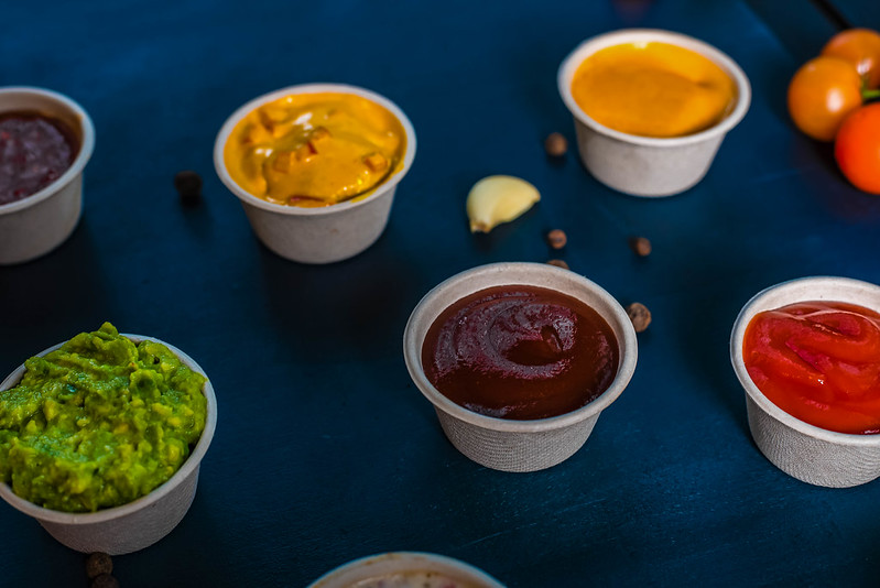 A selection of sauces in small paper cups.